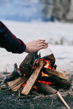Girl warms hands near a fire in winter Stock Photos