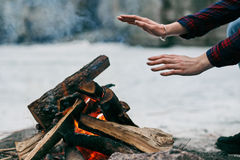 Girl warms hands near a fire in winter Royalty Free Stock Image