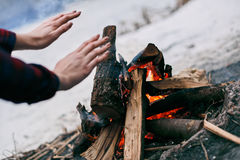Girl warms hands near a fire in winter Royalty Free Stock Photos