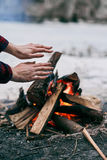 Girl warms hands near a fire in winter Royalty Free Stock Photo