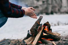 Girl warms hands near a fire in winter Stock Image