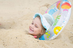 The girl was buried in the sand on the beach and put it under his head round Stock Images