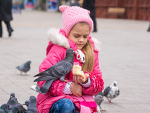 Girl was frightened brazen pigeon who jumped into his arms for a crust of bread Royalty Free Stock Photos