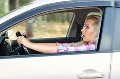 Girl was frightened paints her lips behind the wheel while drivi Stock Image
