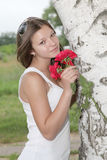 Portrait of a girl with roses under the birch. The girl was in a good mood standing under white birch inhales the scent of a bouquet of red roses Royalty Free Stock Photography