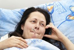 The girl was lying in bed and  the temperature Royalty Free Stock Photography