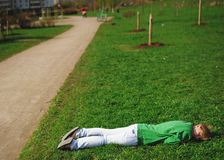 Girl was tired and lay down to relax on the grass near the road royalty free stock photo