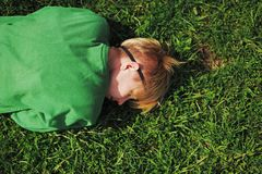 Girl was tired and lay down to relax on the grass near the road. Blonde girl was tired and lay down to relax on the grass near the road Stock Images