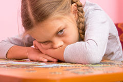 Girl was very tired assemble a picture from puzzles Stock Photos