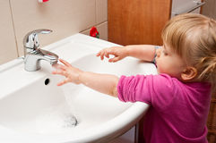 Girl wash hands. Little girl about to wash her hands in the bathroom sink royalty free stock photo