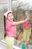 Girl wash window Stock Images