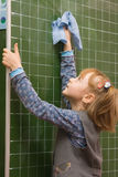 The girl washes a blackboard. The schoolgirl  wipes a blackboard with a rag in a classroom Stock Image