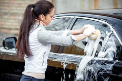 Girl washes the car Royalty Free Stock Images