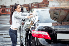 Girl washes the car Stock Image