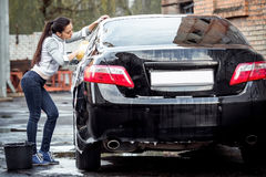 Girl washes the car Stock Photography