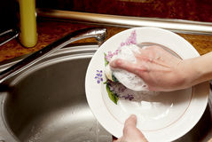 Girl washes the dishes Royalty Free Stock Photos