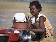 Girl washes dishes on the beach royalty free stock photography
