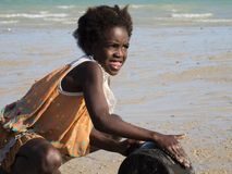 Girl washes dishes on the beach stock photo