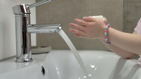 Girl washes hands with soap in the bathroom