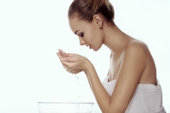 Girl washes her face, leaning over a bowl, and with her hands dr stock photos