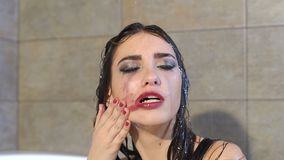 Girl washes makeup in shower under water, her red lipstick smeared on the face. Sexy girl with bright makeup in the shower, she rubs her hand with red lipstick stock footage