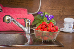 Girl washes strawberries Royalty Free Stock Photo