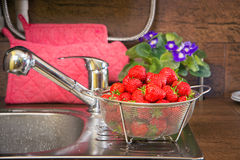 Girl washes strawberries Stock Photos