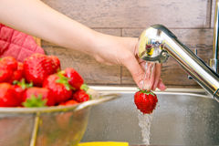 Girl washes strawberries Royalty Free Stock Photography