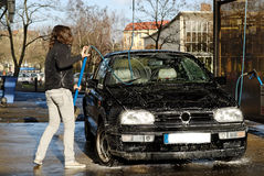 Girl washing car. A girl washing a vw golf stock photo