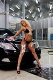 Girl washing a car. A girl in a bikini washing a black car Stock Image