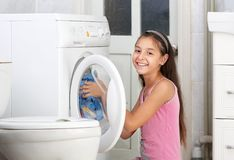 The girl is washing clothes. The beautiful girl is washing clothes in the bathroom Royalty Free Stock Image
