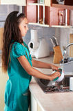 Girl washing dishes in the kitchen Royalty Free Stock Photos