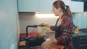 Girl washing dishes in the kitchen cutting board. woman cooks in the kitchen. girl washes a knife on in the sink under stock photos