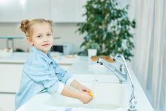 Girl washing dishes Stock Images
