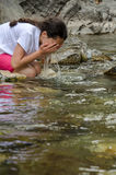 Girl washing face in mountain river Royalty Free Stock Photography