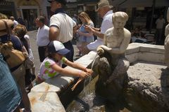 Girl washing hair of Barbie doll in fountain of Amalfi, Italy, Europe, a town in the province of Salerno, in the region of Campani Royalty Free Stock Photos