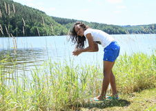 Girl washing hands in lake Royalty Free Stock Photos