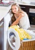 Girl washing  linen at washing machine. Cute girl washing  linen at washing machine Royalty Free Stock Photo