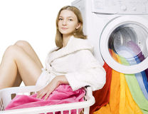 Girl and washing machine. Young girl and washing machine with colorful things to wash, isolated Stock Images