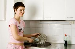 Girl washing the plate. In the kitchen stock images