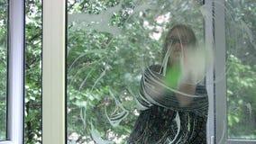 Girl washing window stock footage