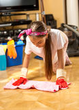 Girl washing wooden floor with cloth at living room Stock Images