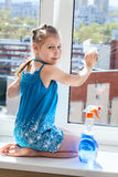 Girl washs windows on windowsill, looking at camera Royalty Free Stock Photo