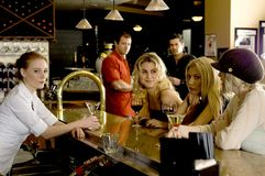Girl watch. Group of girls having fun at the bar, chatting with the bartender, while two hanks watch them with interest from the background Royalty Free Stock Photography