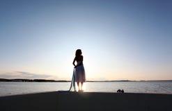 Girl watch sunset. On the beach Stock Photo