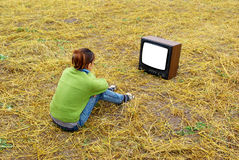 Girl watch TV. On the yellow meadow. Element of design Stock Images