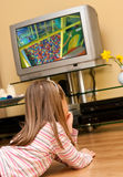 Girl watch TV. A young blond girl watching TV at home Royalty Free Stock Photo