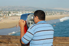 The Girl Watcher. A young man on a pier checking out the sights on the beach through a reto set of binoculars stock photography