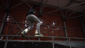 The girl watches as the man performs a grind on the railing, slow motion. A man on rollers performs a grunt trick, in the background a girl watches a trick stock video footage