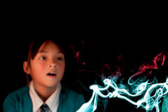 Girl watches colorful smoke. Royalty Free Stock Photos